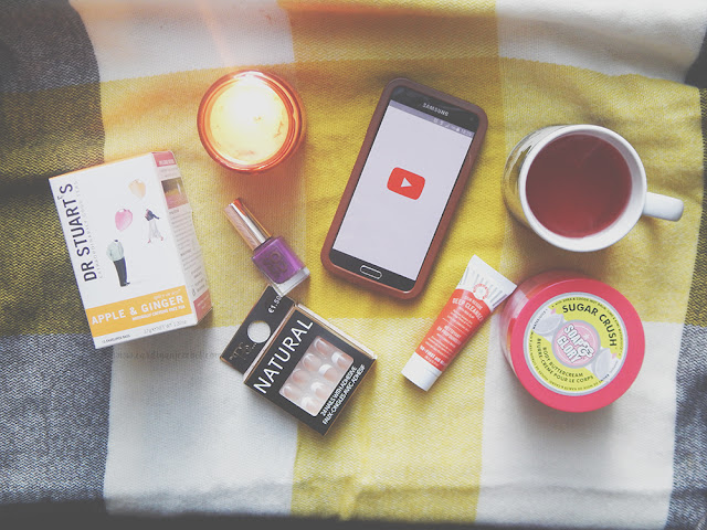 Flat lay picture with a phone, fake nails, nail polish, a face mask, candle, body butter, and a cup of tea.