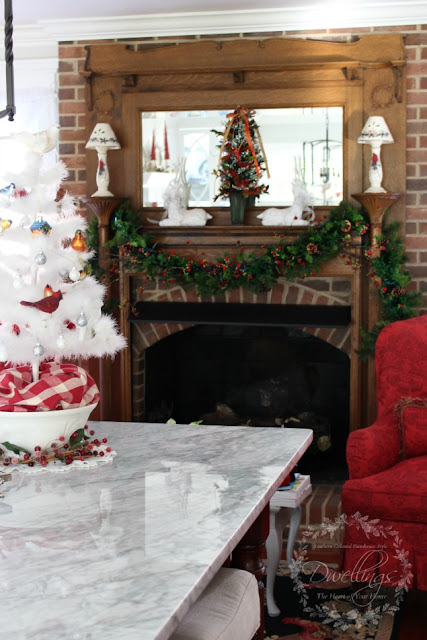 Farmhouse kitchen mantel decorated with garland, a Christmas tree and white glittery deer.