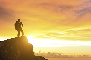 man on top of mountain watching sunset