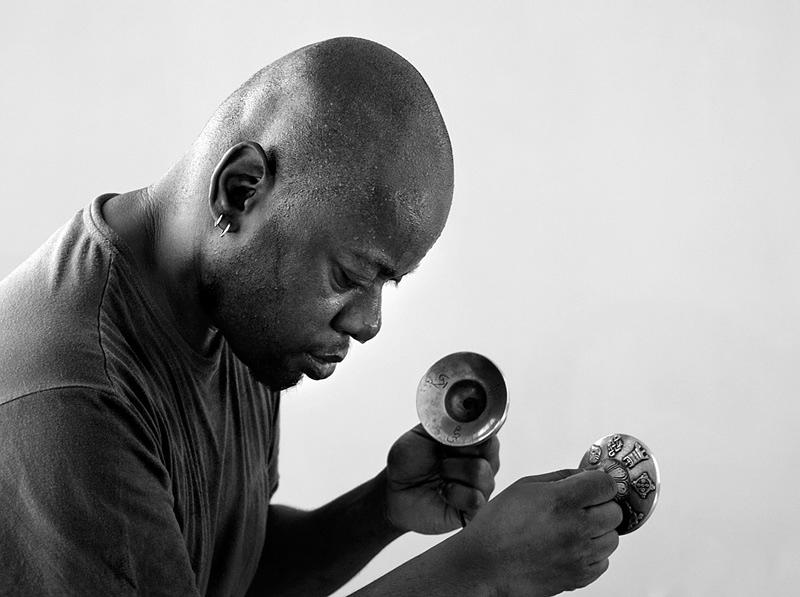 Músico, percursionista, em grande pano, tocando uma espécie de sinos metálicos, pequenos