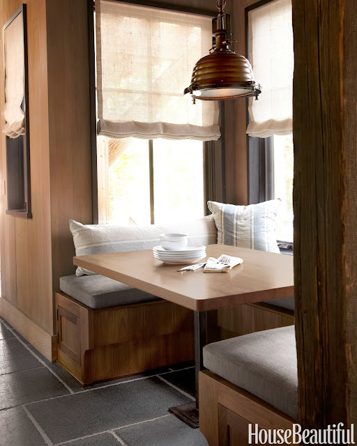 """Banquette in beautiful kitchen. """"Pillows covered in french ticking and bench cushions in Perennials' Ishi make a cozy breakfast nook. 'The industrial light fixture adds structure and weight to the space,' Wick says."""""""