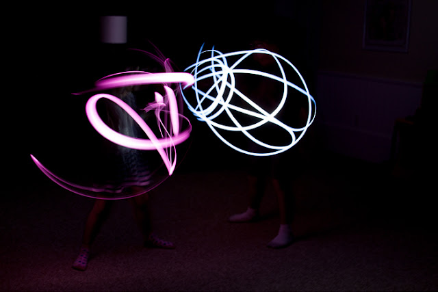 children using flashlights as light sabers and a camera at long shutter speed
