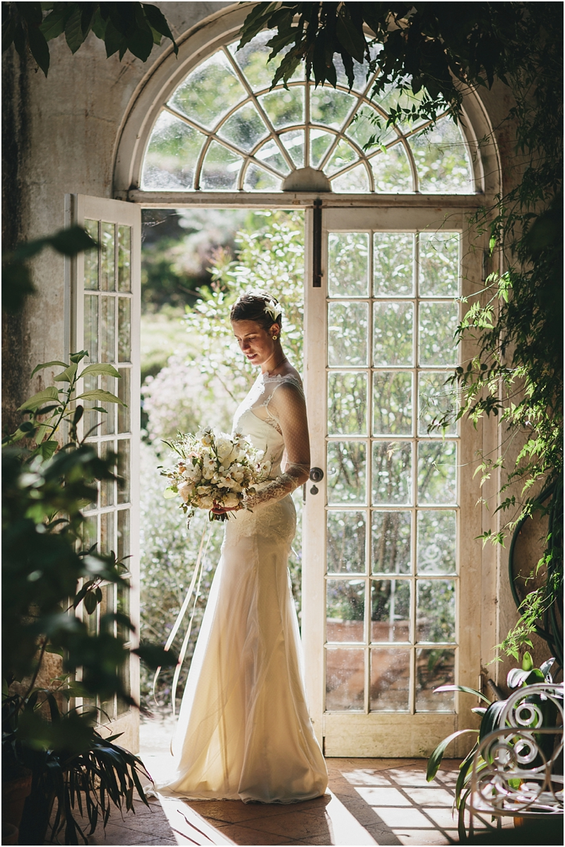 Bride stands in orangery door