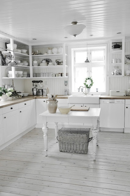 This stunning white themed kitchen has open shelving for dishes and a farmhouse basin kitchen sink