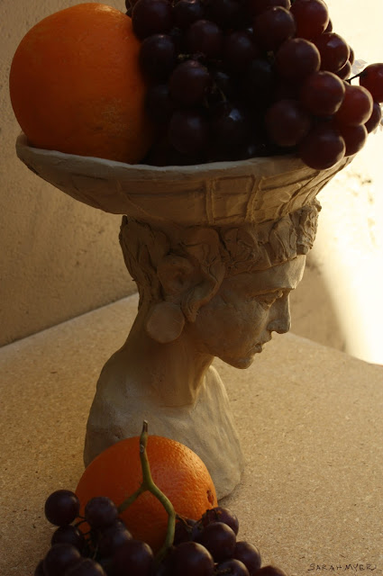 art, sculpture, sarah myers, stoneware, ceramic, escultura, arte, ceramica, fruit, centerpiece, centrepiece, arrangement, figurative, head, woman, basket, bearer, graceful, tranquil, beautiful, food, abundance, plenty, table, face, human, classic, oranges, grapes, pensive, thoughtful