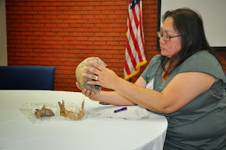 A teacher examines a human skull.