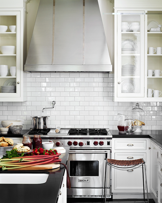 white subway tile backsplash, glass cabinets, steel stove hood kitchen