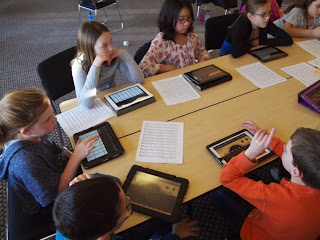 Students in a group working with iPads.