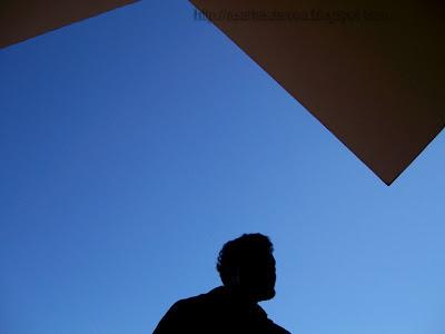 """Fotografia de três siluetas. Silueta do busto de um homem, centralizada na parte inferior e acima nas duas extremidades direita e esquerda da imagem,  a silueta de duas figuras geométricas. O fundo é azul, o azul do céu, completando a composição dessa fotografia feita contra a luz"""" width="""