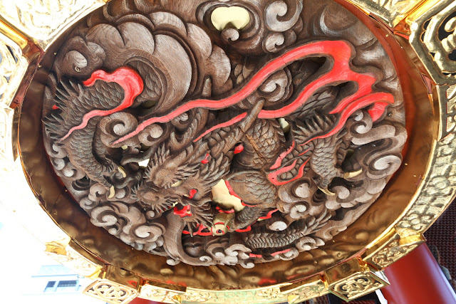 You can find a crafted dragon as you bend and look under the base of the giant red lantern at The Kaminarimo Gate of Asakusa Sensoji Temple in Tokyo, Japan