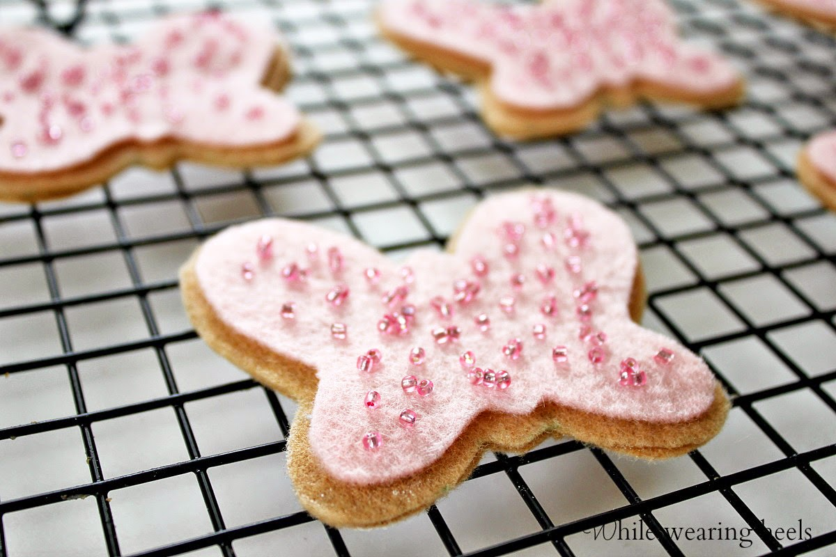 tan felt butterfly cookies with pink felt icing and seed bead sprinkles