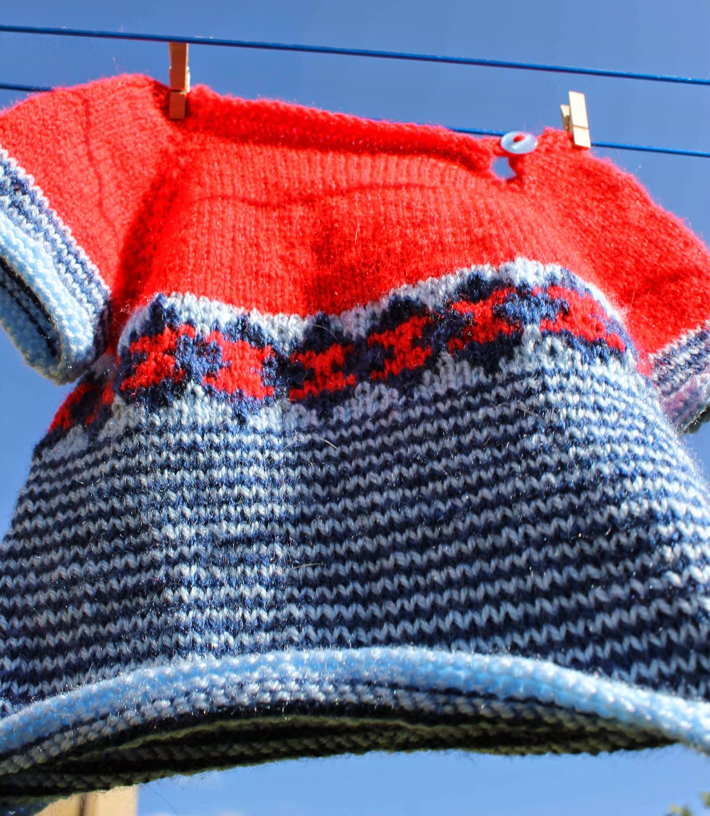 Red and blue striped and patterned knitted jumper
