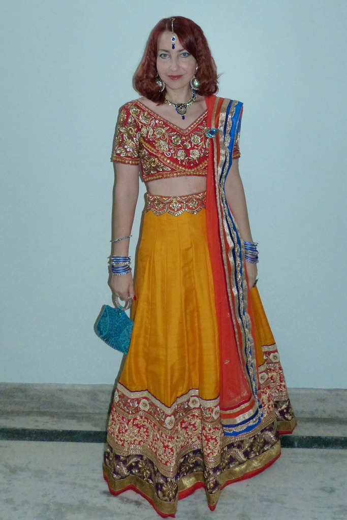 Colourful lehenga choli party outfit worn with peacock theme jewelry and blue purse