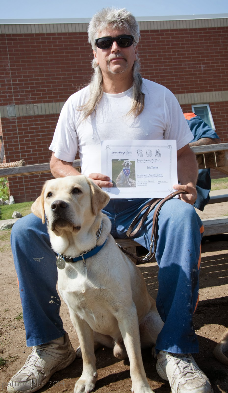 A man wearing sunglasses, blue prison pants and a white t-shirt is sitting in the sun on a picnic bench, facing the camera. Between his legs is a young yellow lab. The man is holding the dog's leash with his left hand on his knee, and a certificale in front of his body with his right hand. There is a brick building behind him. The man has a somber look on his face.