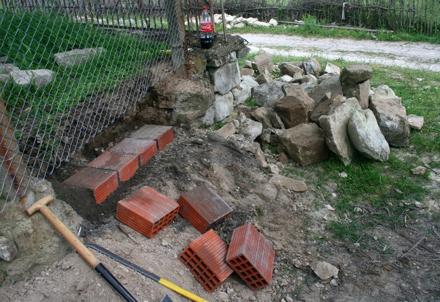 Lots of stone moved, and a course of bricks in place