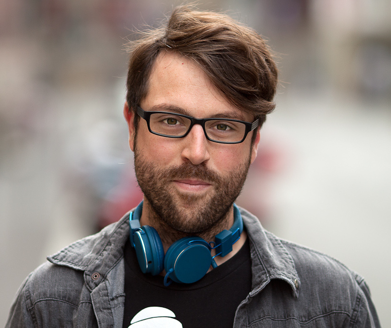 A smiling young chap (man) with a beard and glasses