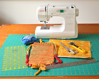 Sewing machine, materials and tools arranged on a cutting mat: quilter's rule, pin cushion with pins, a reel of sewing thread, a swatch of cotton quilting fabric, a rotary cutter, pair of scissors, steel rule and the WIP Project bag.