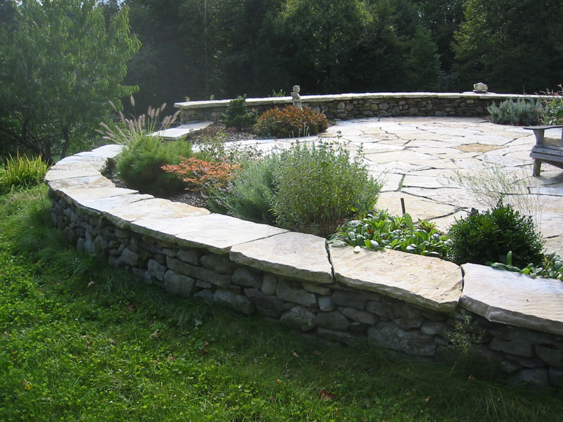 Stone Wall Surrounding Stone Patio by Omni Stone Work