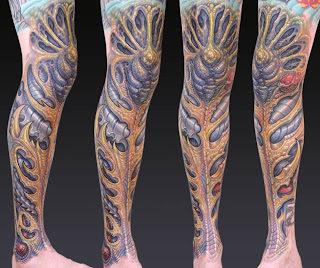 biomechanical tattoo on the leg: alien-like bones and tissues
