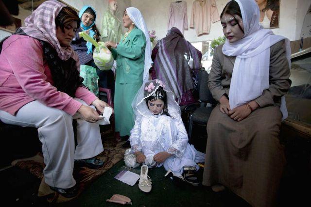 Zahara, una novia afgana de 24 años, se prepara para la ceremonia de la boda rodeada por miembros femeninos de su familia, en un salón de belleza (14 de