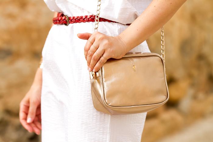 Accesorios rojos y dorados con vestido blanco