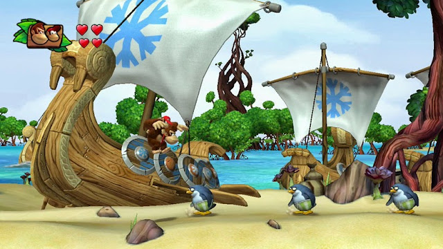 Donkey Kong with Diddy Kong on his shoulders. They are jumping in the air while penguins walk below them on a tropical beach. Screenshot from video game Donkey Kong Country: Tropical Freeze