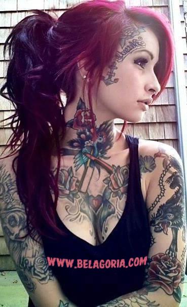 pelirroja apoyada en una pared, lleva tatuajes por todo el cuerpo, son tatuajes tradicionales