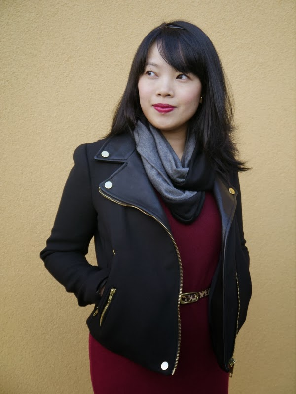 Vancouver blogger Lisa Wong of Solo Lisa wears a black moto jacket, black/grey colourblocked jersey scarf, burgundy sweater dress, and leopard print belt.