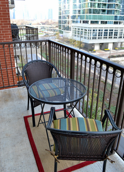 Balcony with two small chairs and a table.