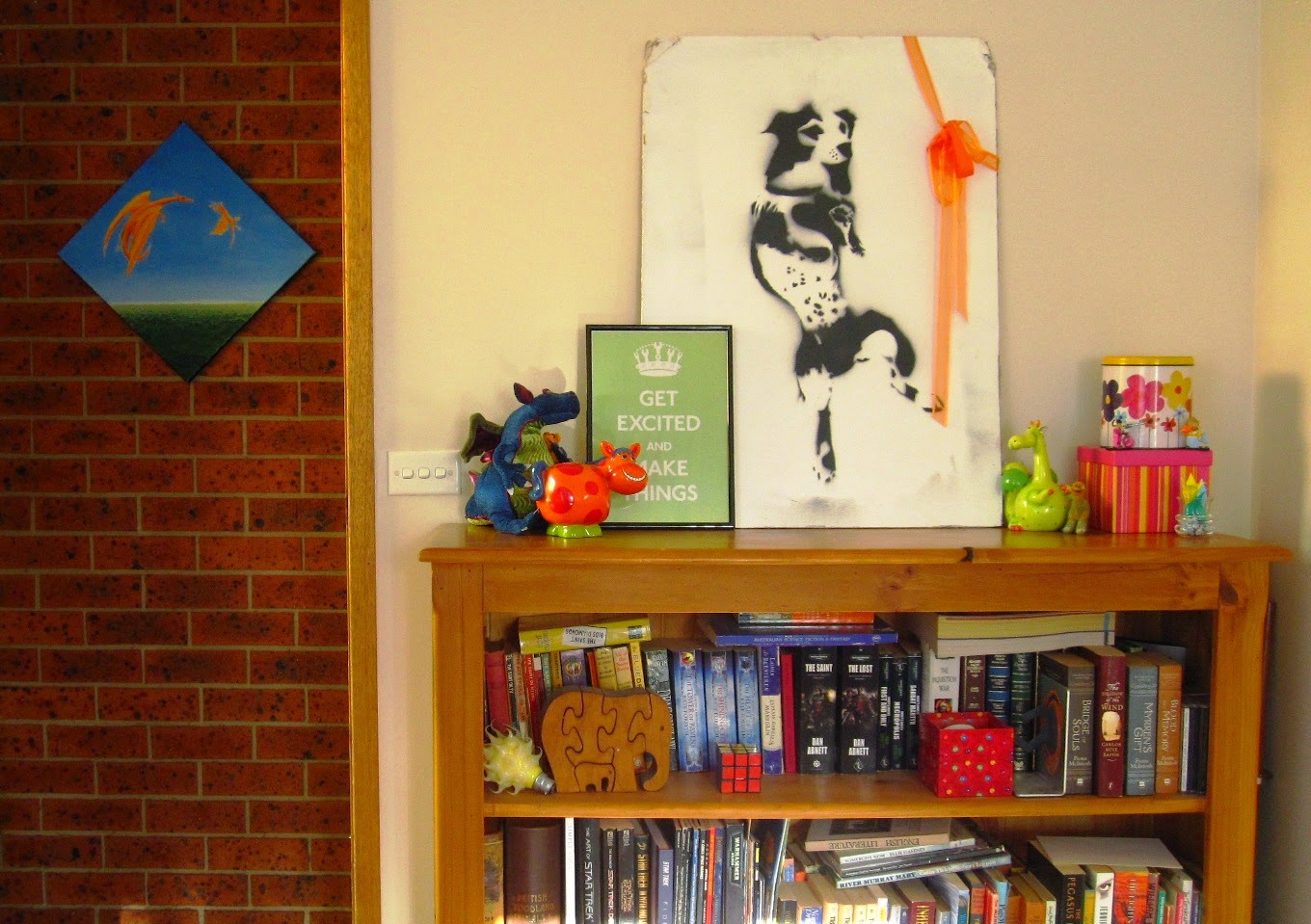 Wooden bookcase in front of a cream wall. On top of the bookcase is a selection of brightly coloured ornaments and a black and white piece of dog street art. There is a brick wall to the left with a painting of orange dragons flying in a blue sky.