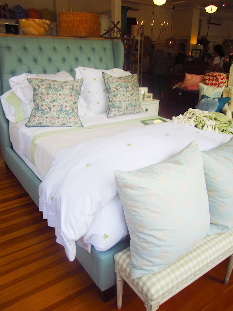 bedroom display in The Lion's Paw with green and white embroidered linens and a gingham bench at the end with a few more COCOCOZY Natural Linen pillows