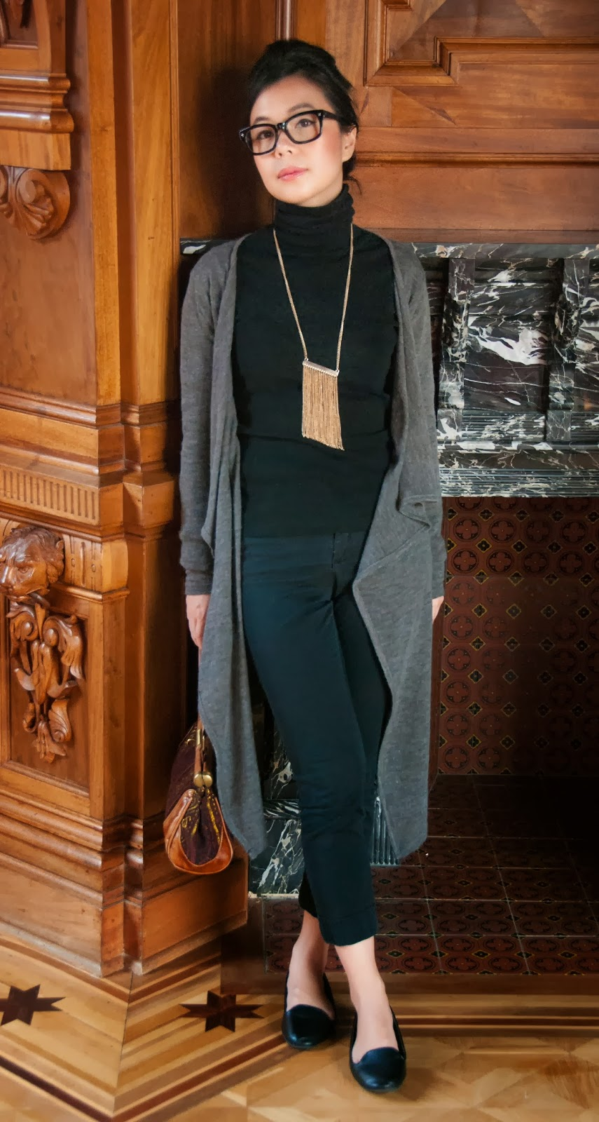 grey cardigan black turtleneck trousers pants statement necklace geek-chic glasses bouffant loafers