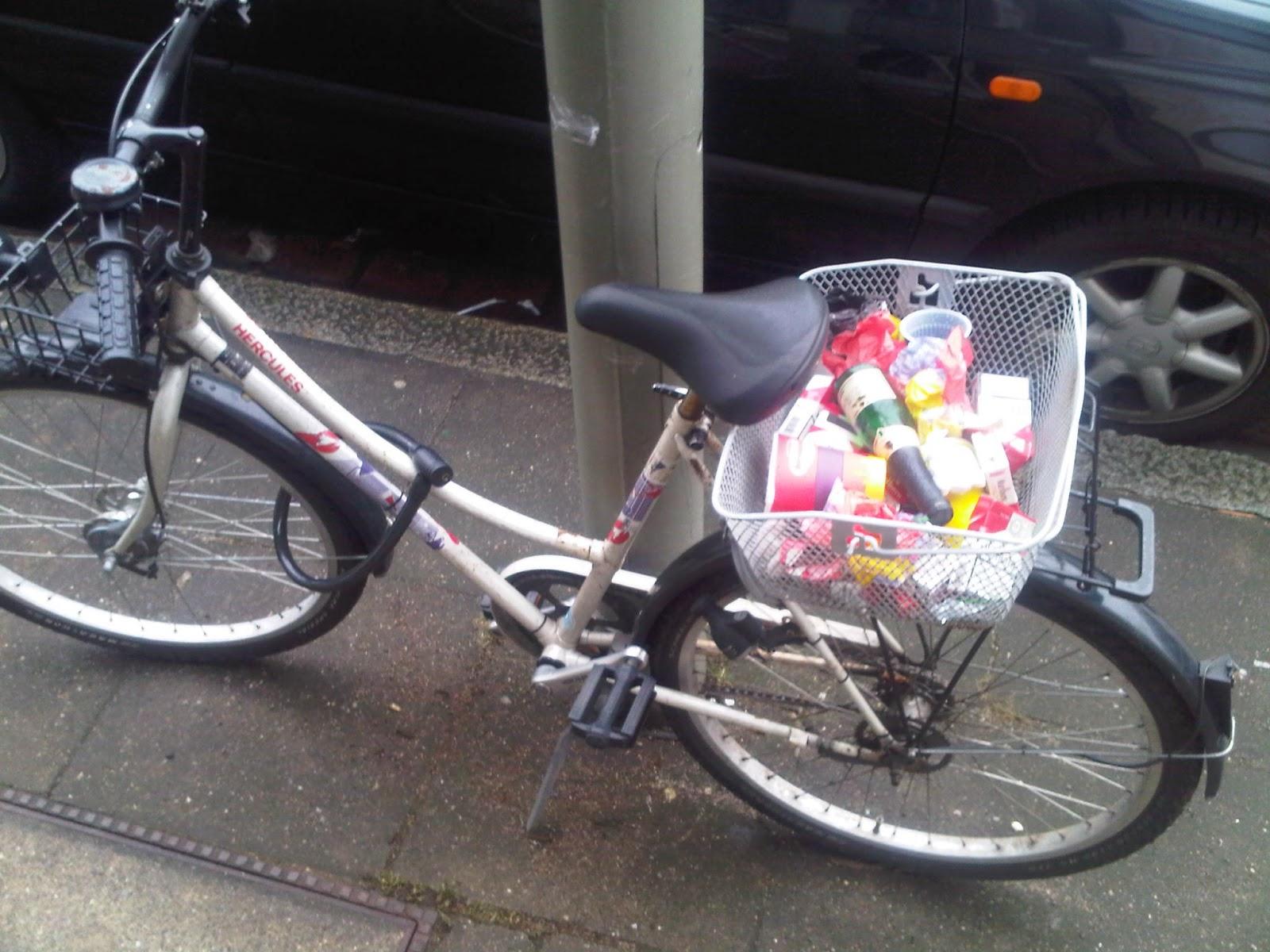 Fahrrad am Straßenrand mit Müll im Korb. Flaschen, Becher, Zigarettenpackungen etc. im Fahrradkorb.