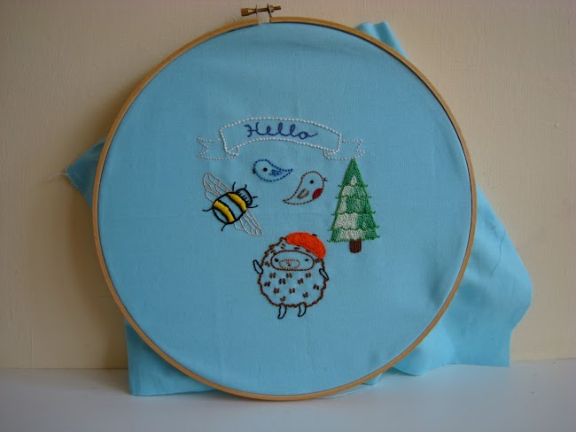 Embroidery of hedgehog wearing a beret, birds, hello on a banner, trees and bee