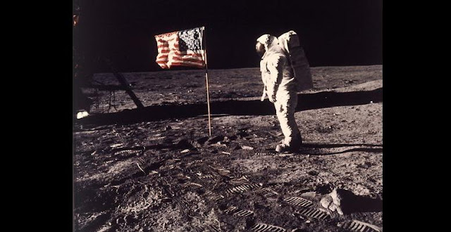 "In this July 20, 1969 file photo, astronaut Edwin E. ""Buzz"" Aldrin Jr. stands next to a U.S. flag planted on the moon during the Apollo 11 mission. Aldrin and Neil Armstrong were the first men to walk on the lunar surface. Credit: Neil A. Armstrong/NASA via AP"