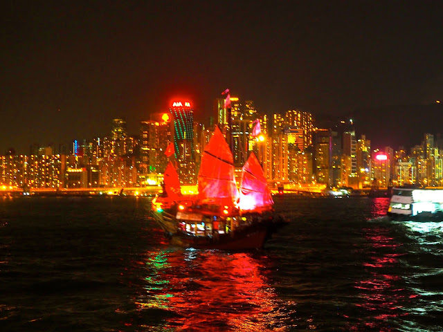 A Symphony of Lights | view of Hong Kong island and Victoria Harbour from TST promenade at night, with traditional Chinese junk boat