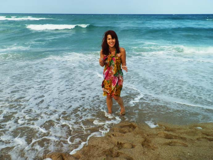 My self on the beach, standing exactly on the seashore, wearing a colorful scarf as  cover up