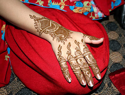 Traditional Indian girl applied Heena on her both palms and it looks like bridal design.