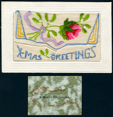 An embroidered card featuring a large red and pink rose with green leaves tied with a lavender ribbon. A blue and yellow decorative border surrounds the bottom-half of the flower. 'X-Mas Greetings' is embroidered below in baby-blue thread. A card with green, white and red decorations reads 'Merry Christmas' and is separate from the embroidered card.