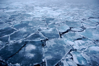 Photo of broken up ice on an unidentifiable body of water