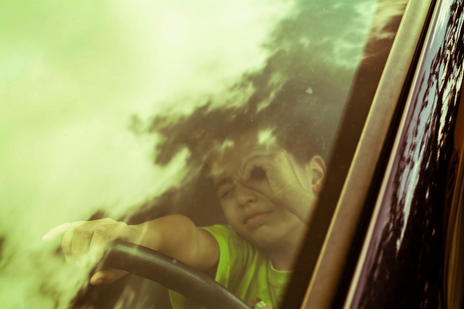Ein Junge schaut durch eine Winschutzscheibe - Autoankauf