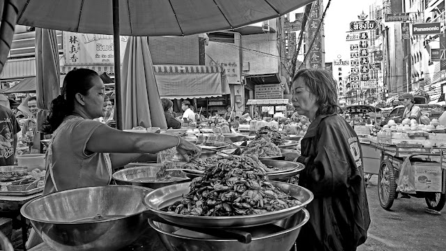 Crab monger and her customer in Chinatown, Bangkok.