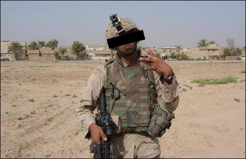 A soldier in a combat zone throwing gang signs