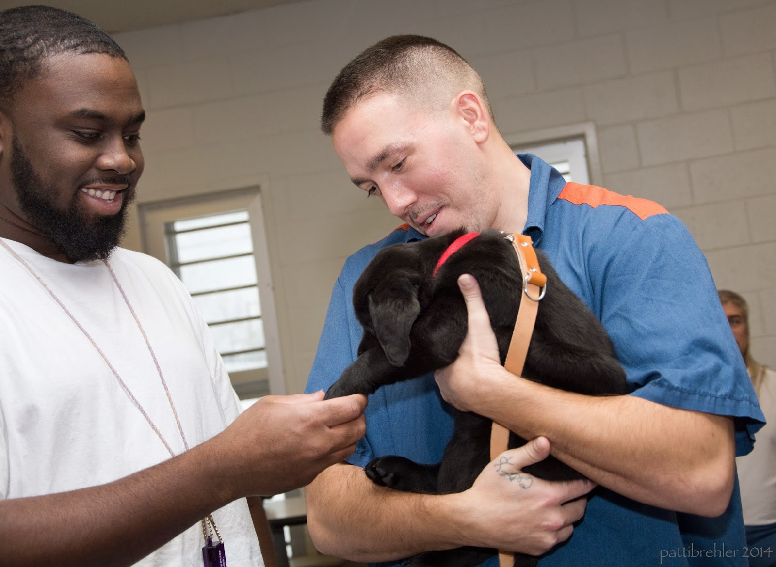 An african american man wearing a white t-shirt is on the left side looking at a black lab puppy being held by another man on the right side. Both men are smiling and looking at the puppy. The man on the left is holding the puppy's front paw with his right hand.