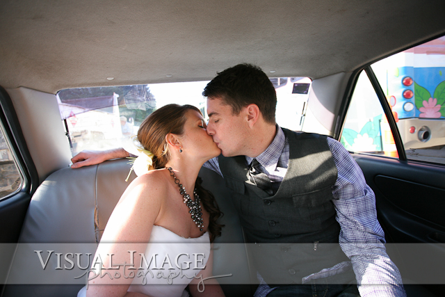 Bride and groom kissing in back of taxi in Playa del Carmen Mexico