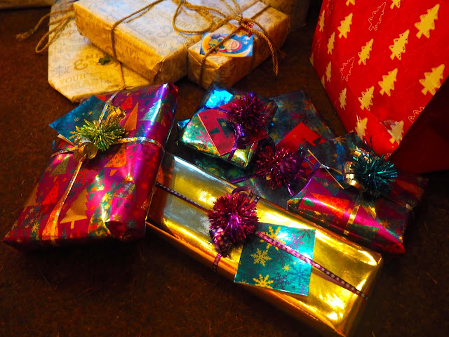 My Christmas presents to my family, wrapped in shiny purple, blue, gold and silver paper and ribbons