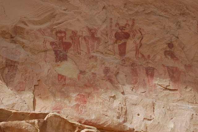 Many red pictographs of alien-like people on a white rock wall in 9 Mile Canyon Utah