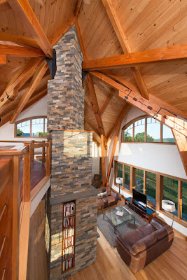 The home design features a central hearth and chimney supporting a timber frame which mimics a canopy of trees in a grove.