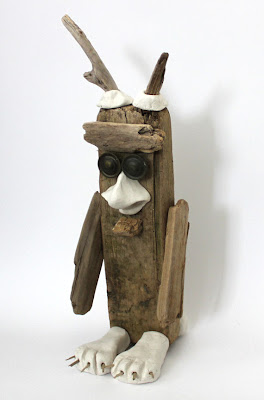 bird like monster sculpture made from clay and wood
