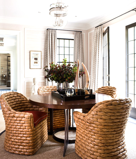 breakfast nook with four chairs made of a large wicker weave surrounding a wooden table with a serving tray holding a vase of flowers, a glass ball and a pair of horns. The room is lit by large black framed windows with floor length patterned curtains